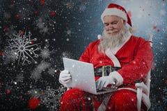键入在膝上型计算机的圣诞老人的综合图象反对白色背景 库存照片