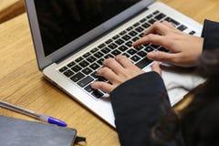 键入在膝上型计算机的女商人在她的书桌 免版税库存图片