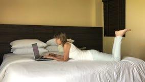 键入在膝上型计算机的女孩在旅馆里 股票录像