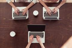 键入在膝上型计算机的女实业家在桌上 库存图片
