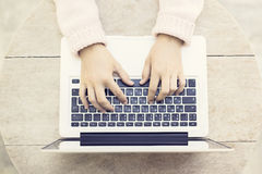 键入在膝上型计算机的妇女在木桌上户外 免版税库存图片