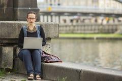 键入在膝上型计算机的妇女坐河的堤防在老镇 库存照片