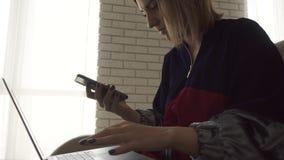 键入在膝上型计算机的妇女特写镜头 然后到达她的电话和看它 女性键入在键盘 自由职业者 股票视频