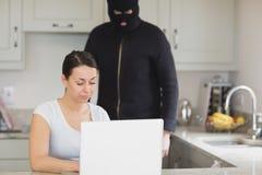 键入在膝上型计算机的妇女,当看它时的夜贼 库存照片