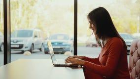 键入在膝上型计算机的妇女,微笑对咖啡馆 配置文件 影视素材