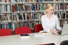 键入在膝上型计算机的学生在大学图书馆里 库存照片