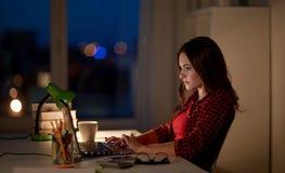 键入在膝上型计算机的学生或妇女在夜家 库存照片