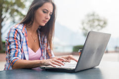 键入在膝上型计算机的少妇学习或运转在公园 免版税图库摄影