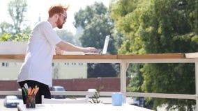 键入在膝上型计算机的年轻人,站立在室外的阳台上 库存照片