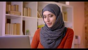 键入在膝上型计算机的年轻可爱的回教女性雇员特写镜头射击是成功的和愉快地微笑 影视素材