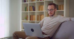 键入在膝上型计算机的年轻英俊的白种人商人特写镜头画象看微笑的照相机愉快地坐 股票录像