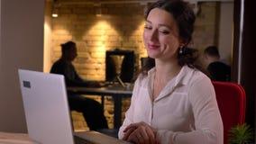 键入在膝上型计算机的年轻迷人的女性办公室工作者特写镜头画象看挥动的照相机微笑和 影视素材