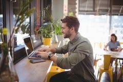 键入在膝上型计算机的微笑的年轻人侧视图在咖啡店 库存照片