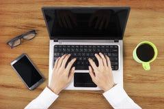 键入在膝上型计算机的手在办公室 免版税库存图片