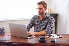 键入在膝上型计算机的时髦人士,当安装在书桌时 图库摄影
