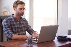 键入在膝上型计算机的时髦人士,当安装在书桌时 库存照片