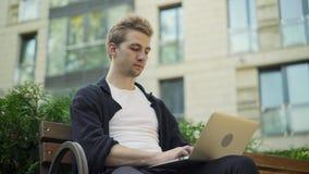 键入在膝上型计算机的白肤金发的人外面 股票录像
