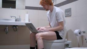 键入在膝上型计算机的红头发人人,坐洗手间洗脸台 图库摄影