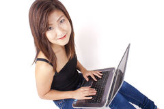 键入在膝上型计算机的美丽的亚裔少妇 免版税库存图片