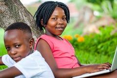 键入在膝上型计算机的逗人喜爱的非洲女孩在兄弟旁边 免版税库存图片