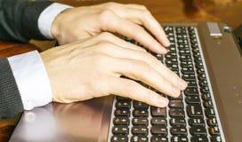键入在膝上型计算机键盘特写镜头的手 背景生意人使用白色的计算机膝上型计算机 库存照片