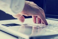 键入在膝上型计算机键盘的人 免版税库存图片