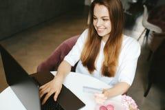 键入在膝上型计算机键盘的兴高采烈的女孩 库存照片