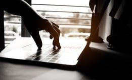 键入在膝上型计算机键盘的匿名黑客的手代码为 库存照片