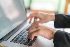 键入在膝上型计算机键盘的女商人手特写镜头 库存图片