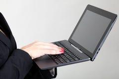 键入在膝上型计算机键盘的女商人 库存图片
