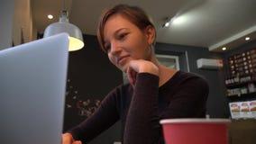 键入在膝上型计算机键盘的女孩在咖啡馆 股票录像