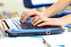 键入在膝上型计算机键盘的女性学习者 免版税库存照片