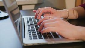 键入在膝上型计算机键盘的女性手文本 免版税库存图片