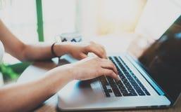 键入在膝上型计算机键盘的女性手特写镜头视图在木桌上 使用机动性的概念年轻现代人民 库存图片