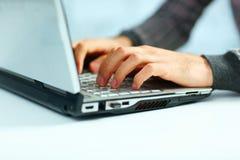 键入在膝上型计算机键盘的男性手 库存照片
