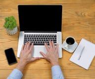 键入在膝上型计算机键盘的男性手 图库摄影