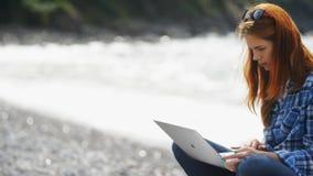 键入在膝上型计算机键盘的繁忙的妇女在海附近 影视素材