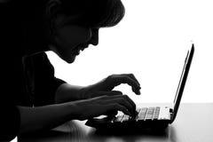 键入在膝上型计算机键盘的黑客的剪影  免版税图库摄影