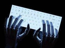 键入在萤光键盘的机器人 免版税库存图片