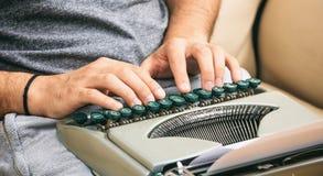 键入在葡萄酒打字机的人手 库存照片