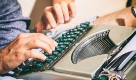 键入在葡萄酒打字机的人手 免版税库存照片