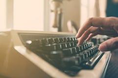 键入在葡萄酒打字机的手 图库摄影