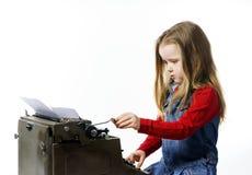 键入在葡萄酒控制台打字机键盘的逗人喜爱的小女孩 库存图片