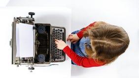 键入在葡萄酒控制台打字机键盘的逗人喜爱的小女孩 免版税库存图片