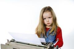 键入在葡萄酒控制台打字机键盘的逗人喜爱的小女孩 免版税库存照片