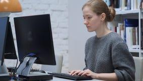 键入在计算机上的红头发人妇女在办公室 库存照片