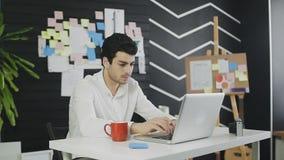键入在计算机上,写下某事和喝咖啡的英俊的商人 股票录像