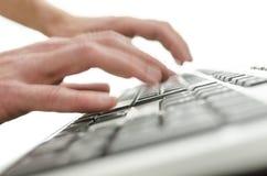 键入在计算机键盘的被弄脏的手 免版税图库摄影