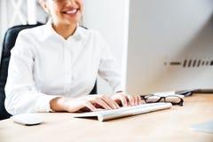 键入在键盘的一名微笑的愉快的女实业家的播种的图象 免版税库存图片