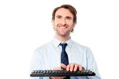 键入在键盘的商人 免版税库存照片